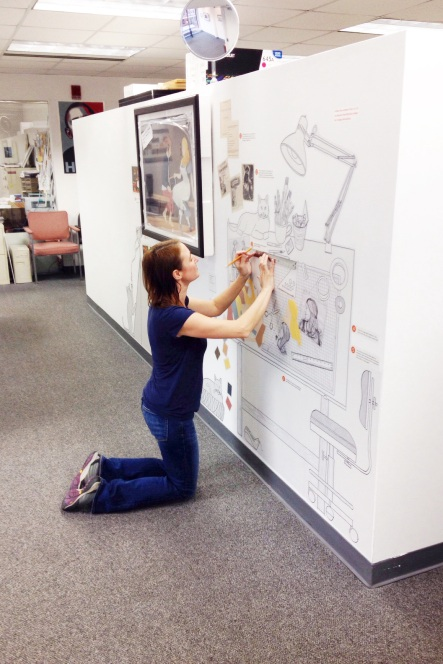 Featured artist/curator Marcela Staudenmaier putting the finishing touches on The Art of Picture Books exhibition.